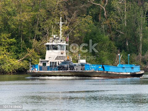 "Westport, Oregon, USA - August 07, 2018: The Wahkiakum County ferry travels between Cathlamet, Washington and Westport, Oregon. The ferry ""Oscar B"" can be seen near the Oregon ramp, after about a 10 minuet crossing from Washington State. Cars can be seen, with the drivers about ready to arrive in Oregon."
