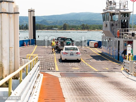 "Cathlamet, Washington, USA - August 07, 2018: The Wahkiakum County ferry travels between Cathlamet, Washington and Westport, Oregon. The ferry ""Oscar B"" can be seen loading on the Washington side, Puget Island. A ferry worker is collecting the crossing fee as the cars arrive on deck."