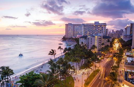 Waikiki Beach and Kalakaua Avenue in Honolulu, HI at night.