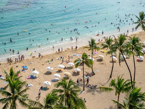 Sun lovers on Waikiki beach in Honolulu.