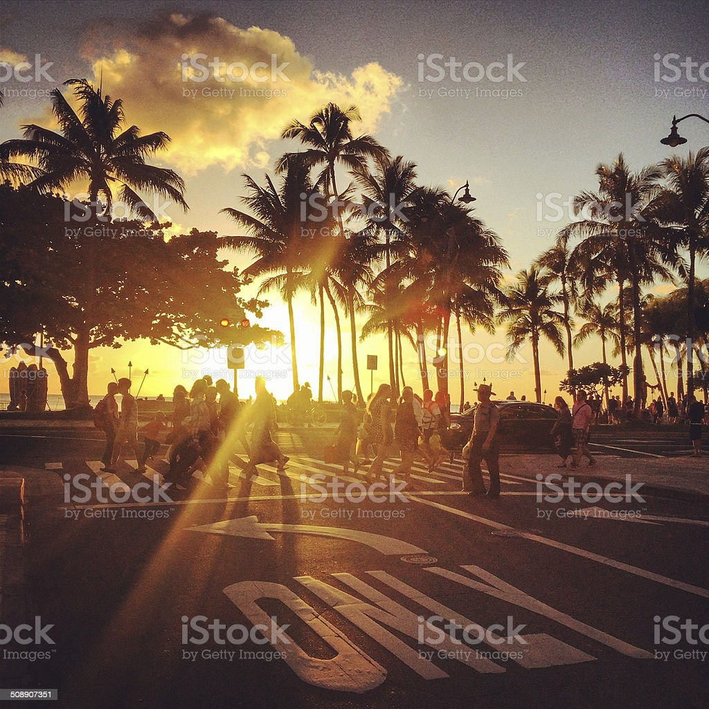 Waikiki beach sunset. people crossing street stock photo