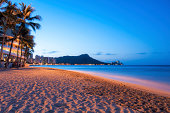 The sun starts to rise over the sand and shore of Waikiki Beach with Diamond Head in the background, Hawaii.
