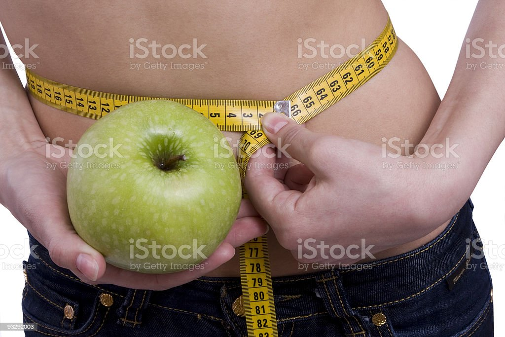 Waist is 65.5 centimeters. Woman, measure tape, apple royalty-free stock photo