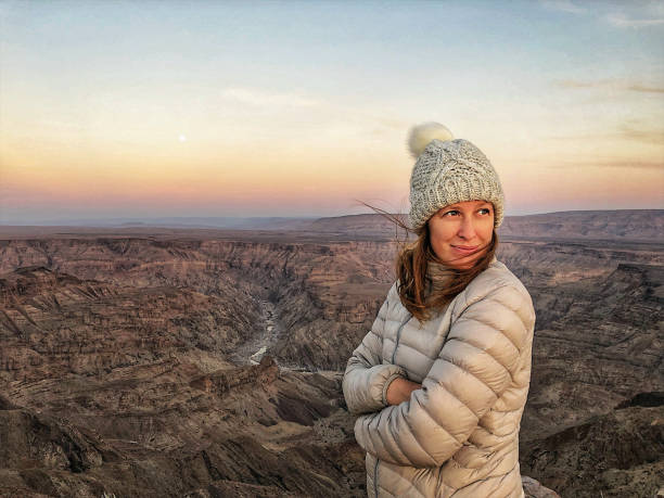 Waist up HDR portrait of Beautiful Woman above a Canyon at sunrise stock photo