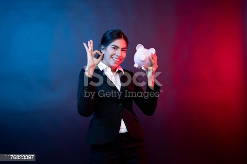 Waist up of 20-29 years old beautiful / handsome people black hair / long hair latin american and hispanic ethnicity female / young women in front of black background who is smiling / happy / cheerful / successful and holding piggy bank / currency / black color / investment / retirement / savings / wealth / sensuality / seduction