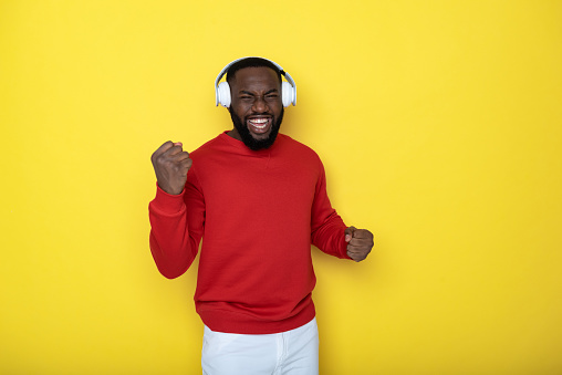Half length of smiling guy with earbuds showing victory gesture with fists against yellow background. He is wearing red sweater and posing for camera in studio. Copy space in right side