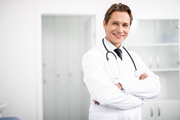 Waist up of happy doctor standing with arms crossed and smiling stock photo