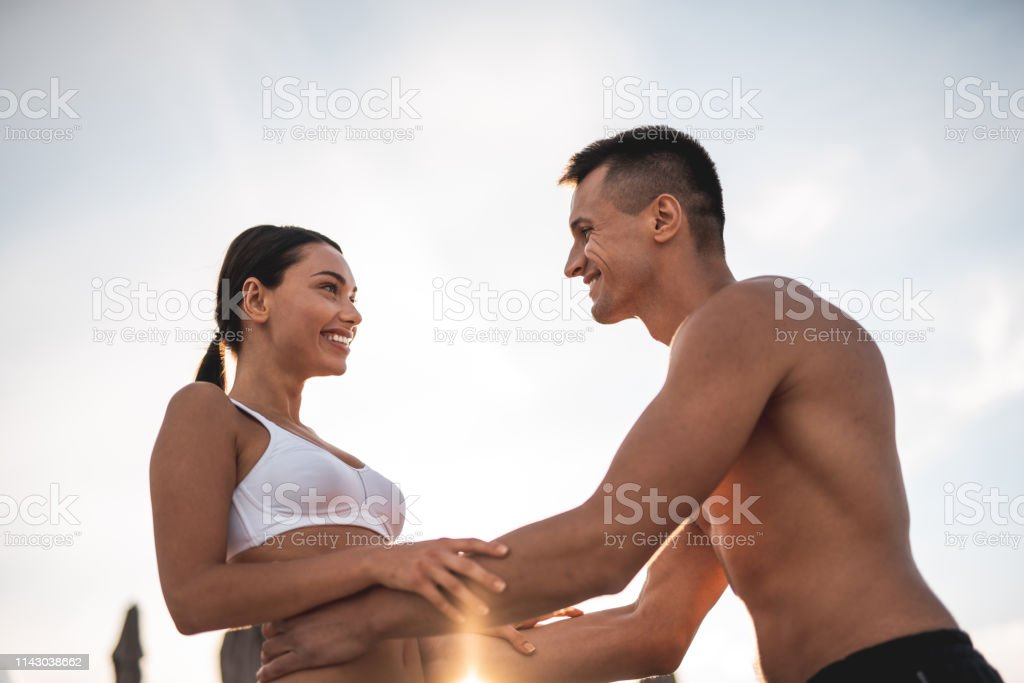 Young cheerful lady in white swimsuit smiling to her beloved man...