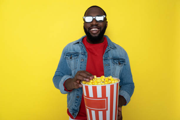 Waist up of smiling African guy holding bucket with popcorn indoors stock photo