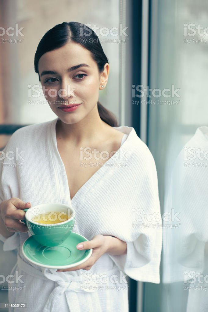 Calm young woman in a white bathrobe standing near the window and...