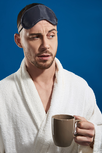 Close up of Caucasian bearded guy wearing white bathrobe and night eye patches while holding cup with tea against blue background. Cropped shot of male model posing for camera while looking away in studio. Morning procedures concept