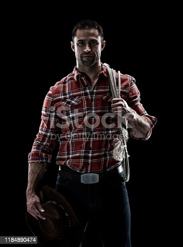 Waist up / one man only / one person of adult handsome people caucasian young men / male cowboy standing in front of black background wearing lumberjack shirt / plaid shirt / button down shirt / shirt / jeans / pants / cowboy hat / hat who is a sex symbol / of muscular build and holding lasso / using rope / black color / sensuality / macho