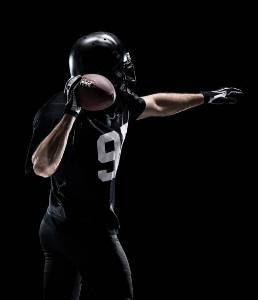 Waist up / one man only / one person / rear view / back of adult handsome people caucasian young men / male american football player / athlete standing in front of black background wearing helmet / sports helmet who is throwing / catching stock photo
