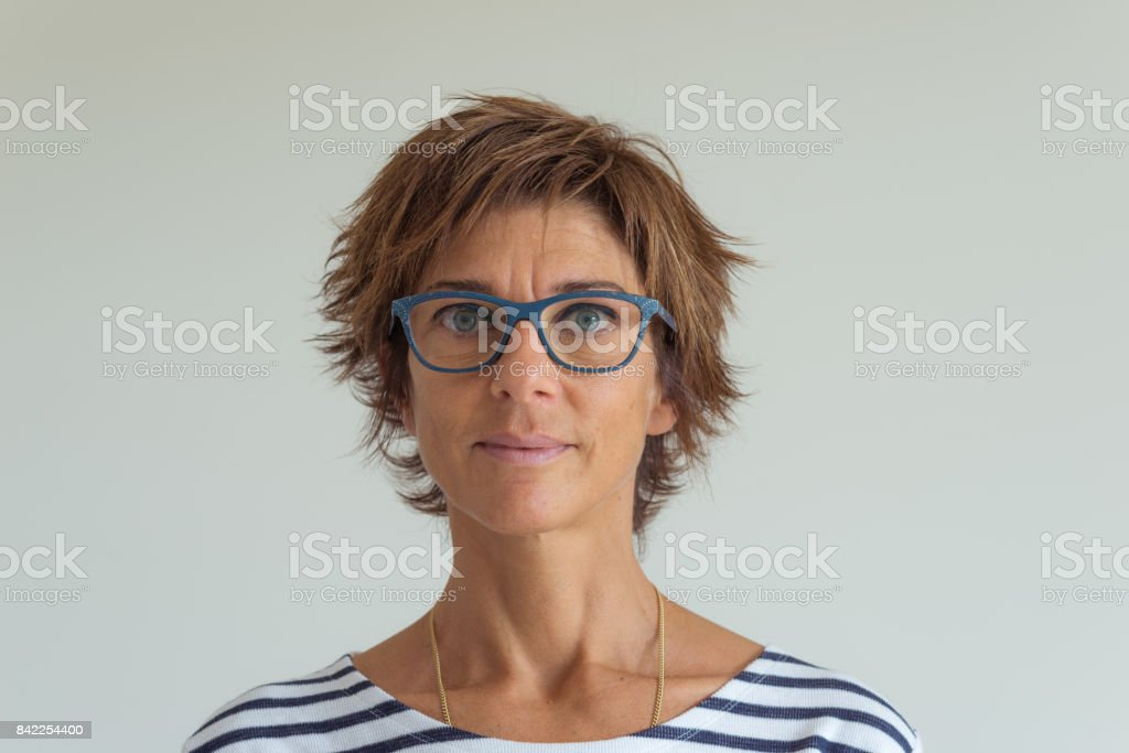 Waist up portrait of adult woman with red hairs, green blue eyes, eyeglasses and cheerful facial expression, in neutral background. Natural soft daylight, natural skin, real people. royalty-free stock photo