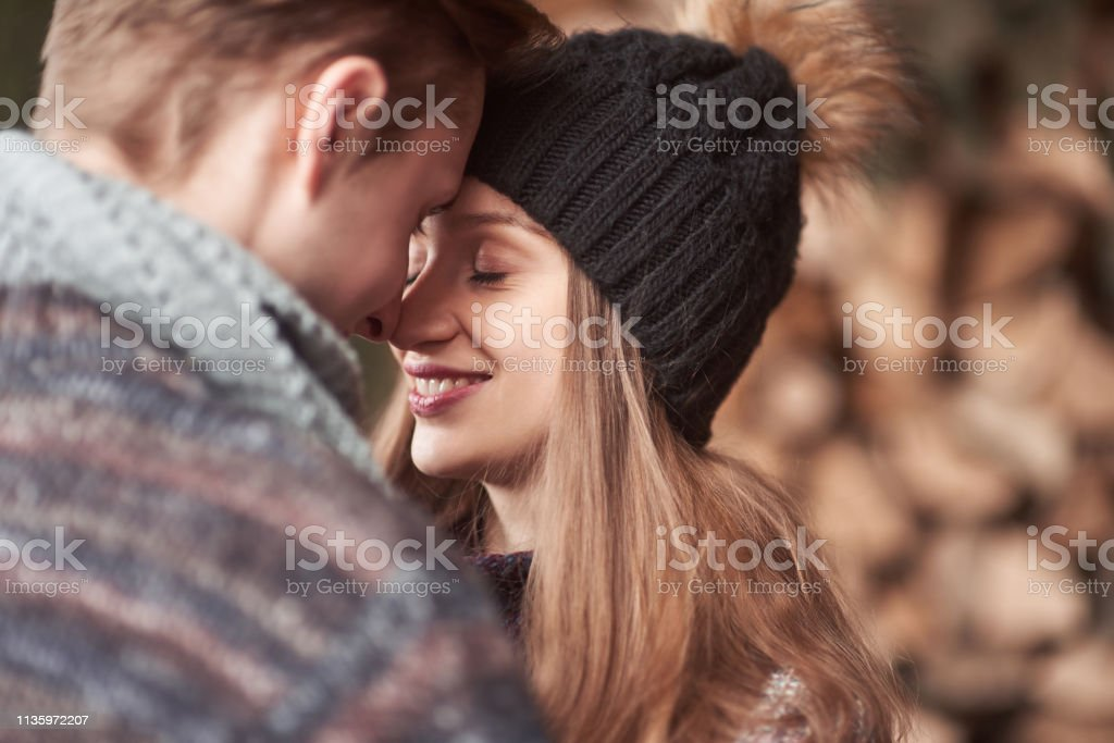 Waist up portrait of carefree young man and woman embracing and...