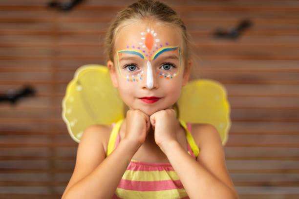 Taille bis Porträt von niedlichen Vorschulkind mit DIY Gesicht Farbe trägt einen Schmetterling Halloween oder Karneval Kostüm. – Foto