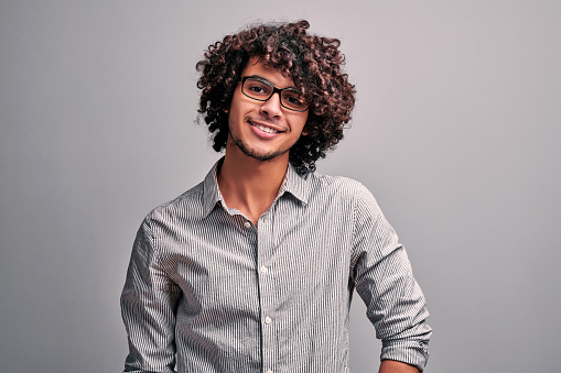 Waist up portrait of handsome eastern guy in gray shirt wearind eyeglasses on isolated gray background. Arabian man with exotic curly hairstyle