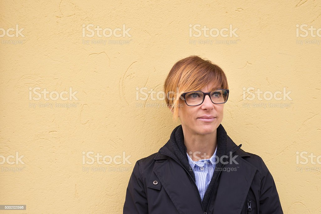 Waist up portrait of lady on yellow plastered wall background stock photo