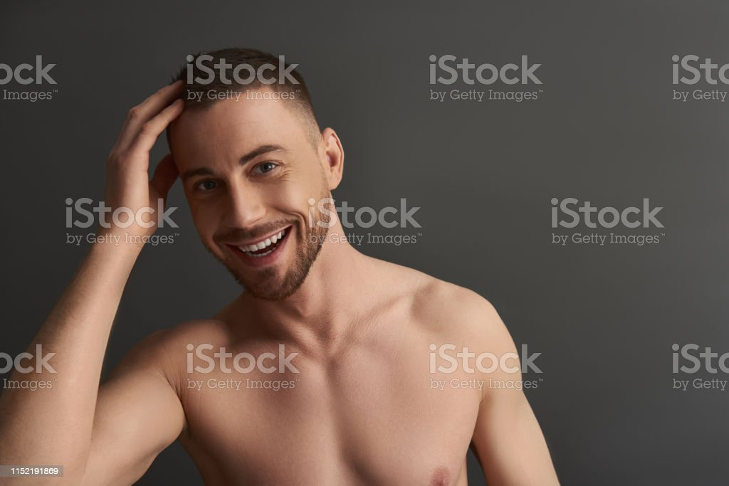 Cropped photo of naked attractive Caucasian guy posing for camera. He...