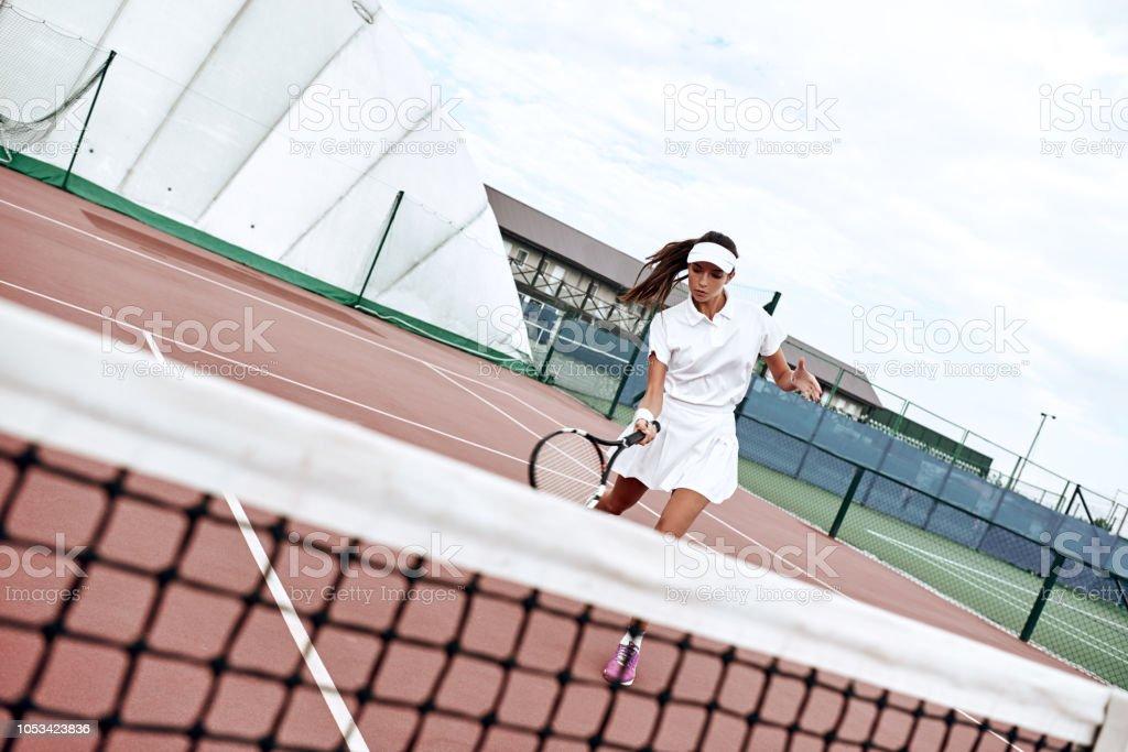 Waist up portrait of positive lady having tennis match on sunny day....