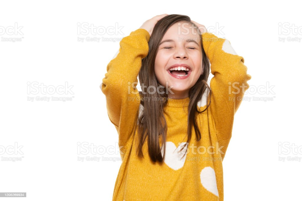 Waist up studio portrait of an adorable young girl laughing with excitement, head in hands and closed eyes, isolated on white backgroud. Human emotions and facial expressions concept. Waist up studio portrait of an adorable young girl laughing with excitement, head in hands and closed eyes, isolated on white backgroud. Human emotions and facial expressions concept. 8-9 Years Stock Photo