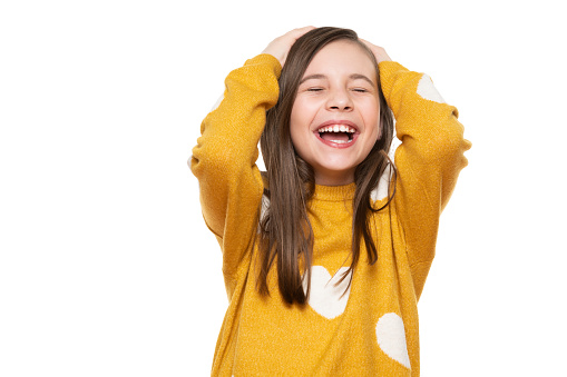 Waist Up Studio Portrait Of An Adorable Young Girl Laughing With Excitement Head In Hands And Closed Eyes Isolated On White Backgroud Human Emotions And Facial Expressions Concept Stock Photo - Download Image Now