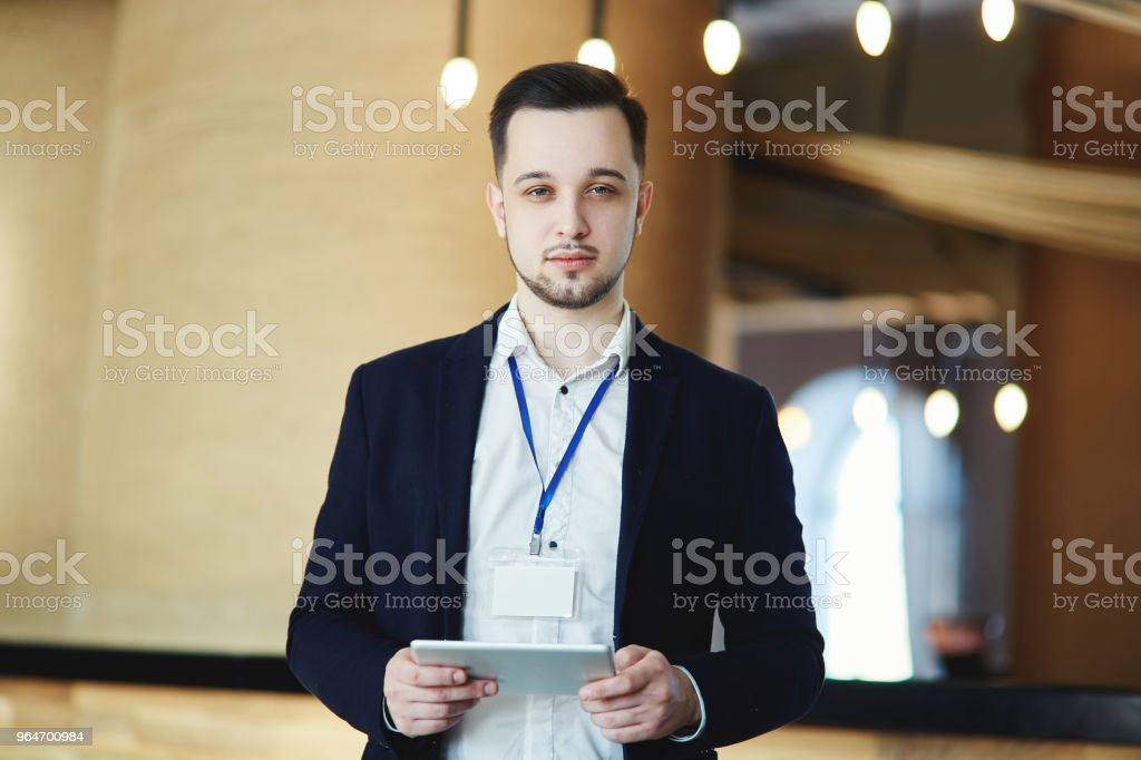 Waist-up portrait of business conference attendee looking at camera with tablet computer in his hands, empty badge around his neck royalty-free stock photo