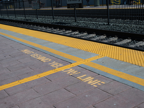 Wait behind yellow line warning on ground on a train platform