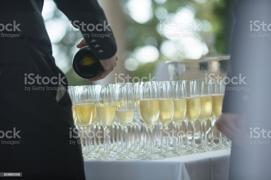 Wait staff pouring champagne in flutes stock photo