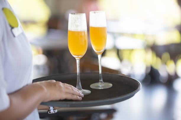 Die Bedienung serviert Mimosa cocktail – Foto