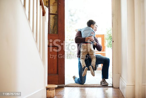 Shot of a little boy running into his father's arms as he arrives at home