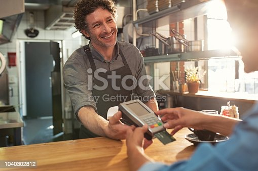 Woman paying by credit card and entering pin code on reader holded by smiling barista in cafeteria. Customer using credit card for payment. Mature cashier wearing apron accepting payment over nfc technology.