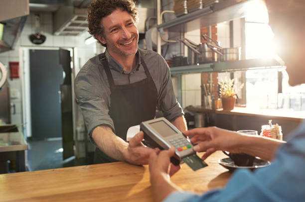 waiter accepting payment by card - credit card imagens e fotografias de stock