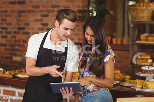Waiter and pretty customer pointing on tablet computer at coffee shop