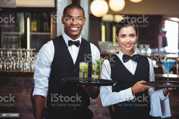 Waiter and waitress holding a serving tray with glass of cocktail picture id661130682?b=1&k=6&m=661130682&s=612x612&h=ubnxhhxgxugexmrozt9xubzv6u2f95deecx9hxmrvdu=