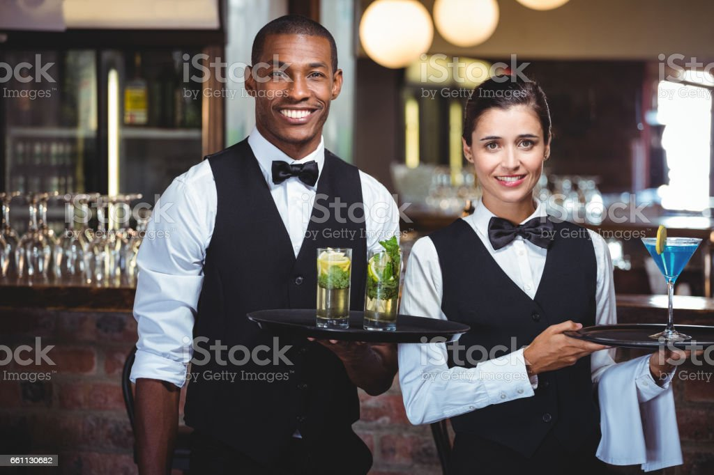 Waiter and waitress holding a serving tray with glass of cocktail stock photo