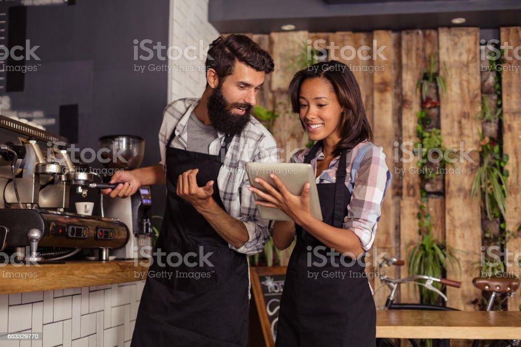 Waiter and waitresses using laptop while working stock photo