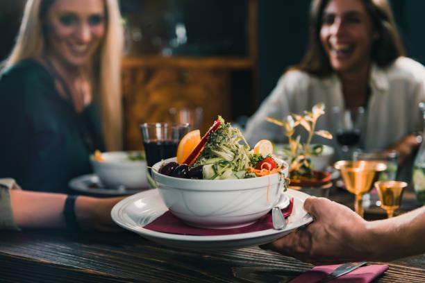 Kellner bringt einen Teller mit vegetarischer Mahlzeit. – Foto