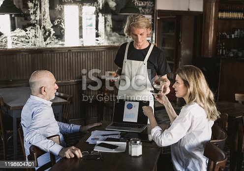 Two business people having  conversation in a restaurant. Waiter bringing them coffee they ordered.
