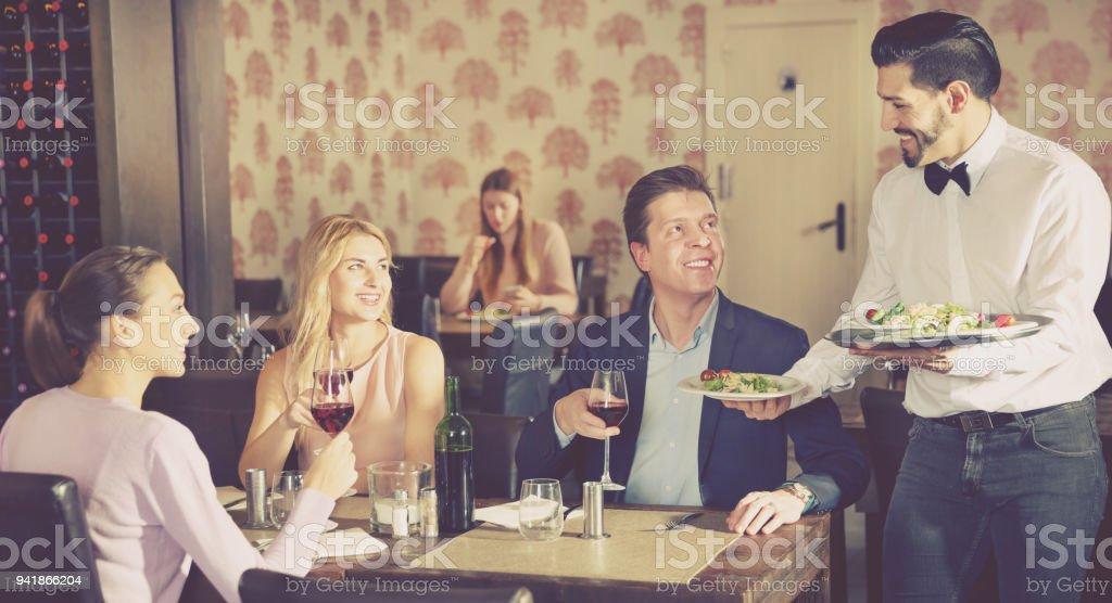 Waiter bringing delicious salads to visitors of restaurant stock photo