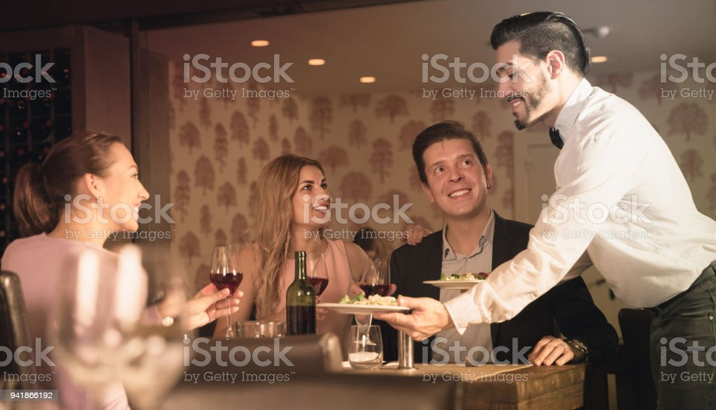 waiter bringing ordered dishes to guests stock photo