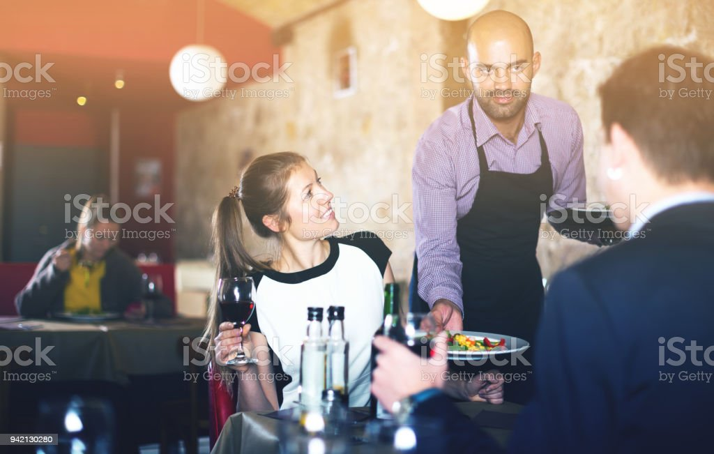 Waiter bringing salads to guests stock photo