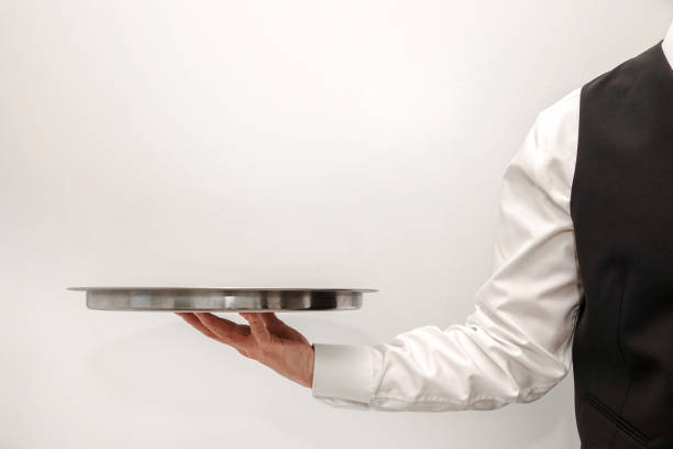 Waiter / butler carrying an empty silver tray stock photo
