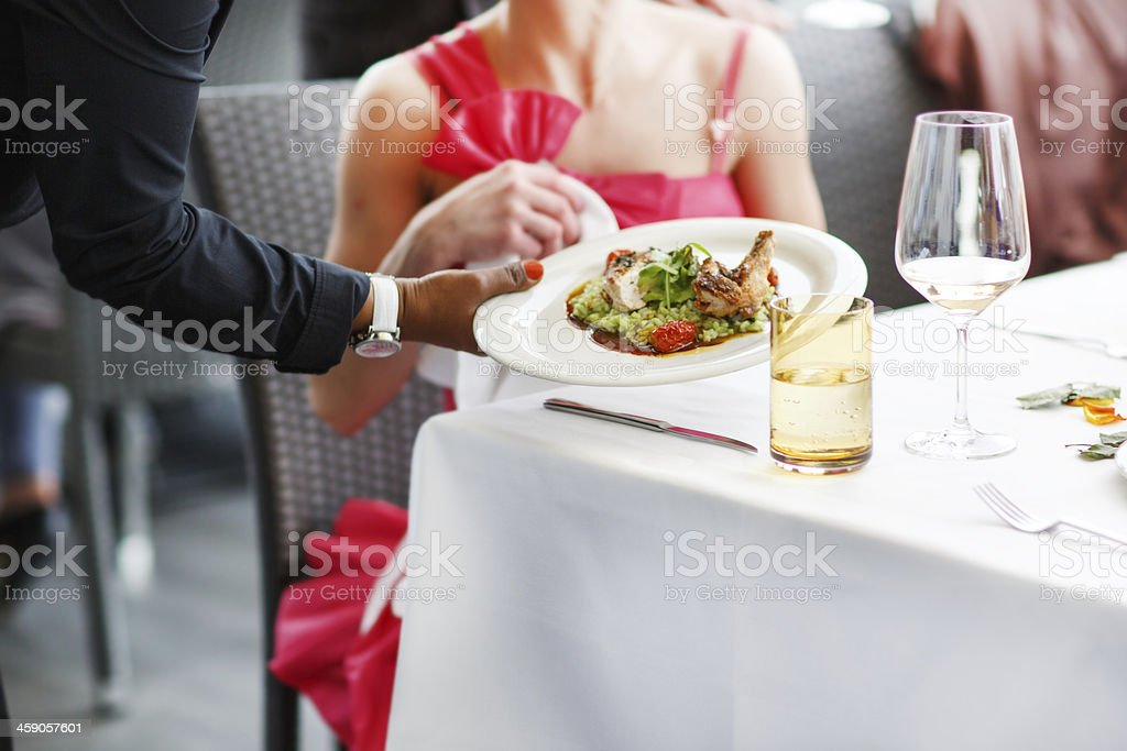 Waiter carrying a plate with salad dish on wedding. stock photo