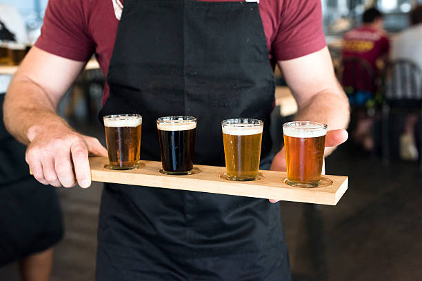 Waiter Carrying a Tray Of Craft Beer In Glasses stock photo