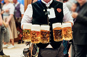 waiter carrying a lot of beer glasses in beer garden at Octoberfest in Munich