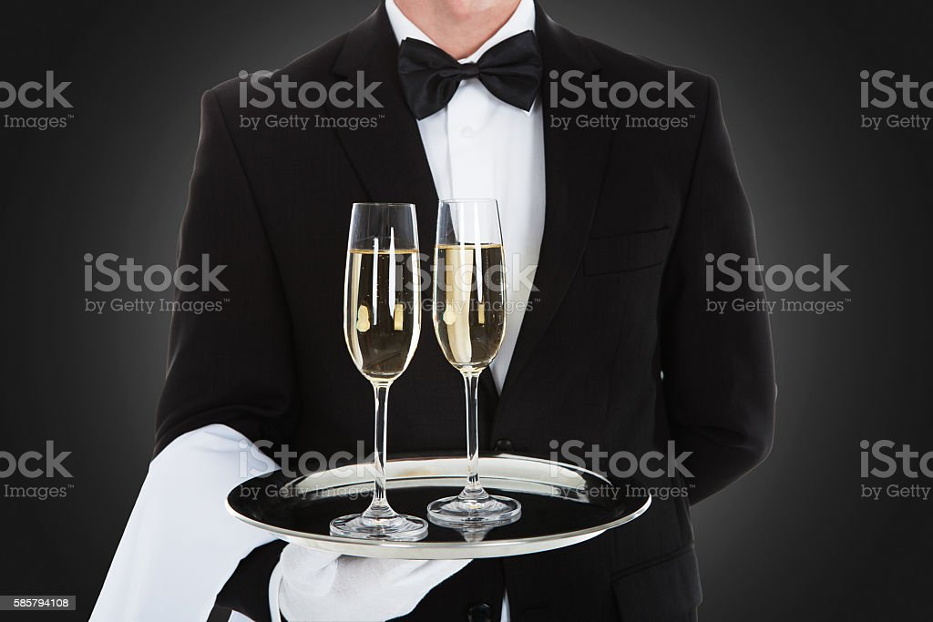 Waiter Carrying Champagne Flutes On Tray stock photo