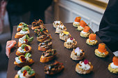 Waiter doing catering service with meat, cheese canepe dish at social gathering festive event party or wedding reception