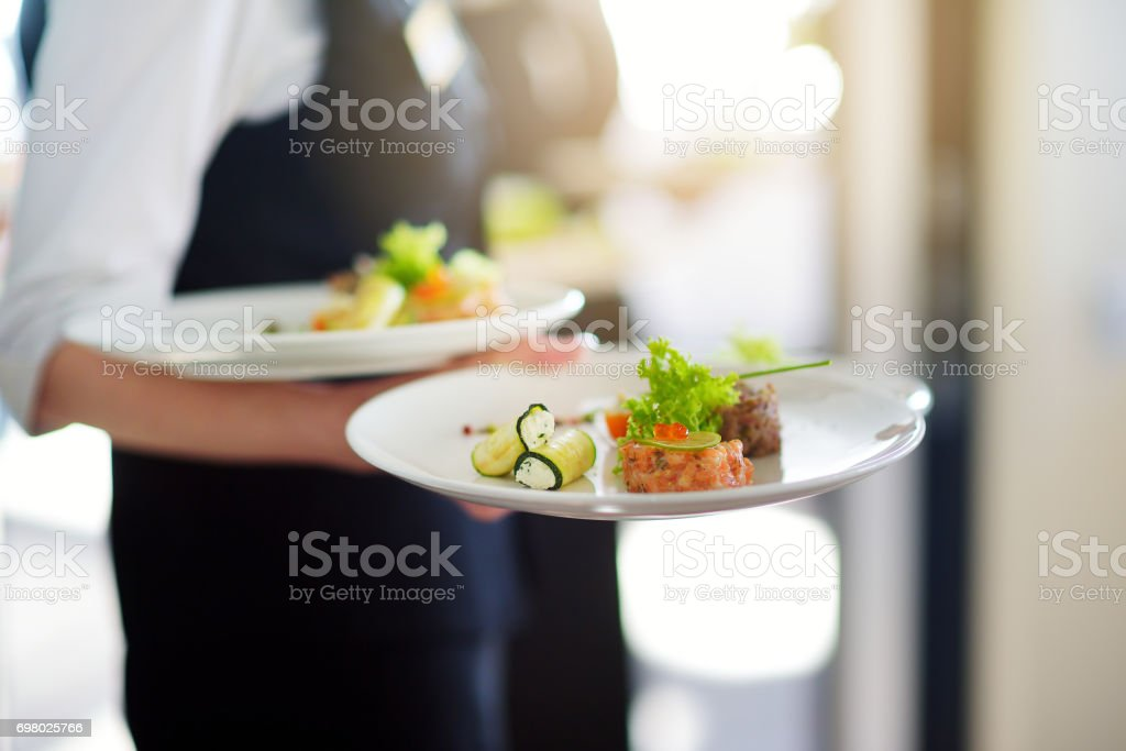 Waiter carrying plates with meat dish on some festive event stock photo