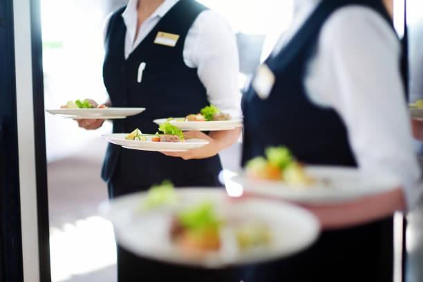 waiter carrying plates with meat dish - униформа стоковые фото и изображения